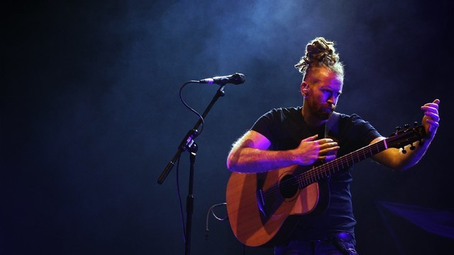Newton Faulkner Performing on Stage with Guitar